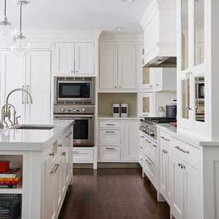 Mid-sized transitional eat-in kitchen remodeling - Eat-in kitchen - mid-sized transitional l-shaped dark wood floor eat-in kitchen idea in New York with a farmhouse sink, shaker cabinets, white cabinets, quartz countertops, gray backsplash, ceramic backsplash, paneled appliances and an island