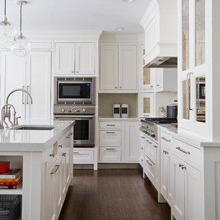 Mittelgroße Klassische Wohnküche in L-Form mit Landhausspüle, Schrankfronten im Shaker-Stil, weißen Schränken, Quarzwerkstein-Arbeitsplatte, Küchenrückwand in Grau, Rückwand aus Keramikfliesen, Elektrogeräten mit Frontblende, dunklem Holzboden und Kücheninsel in New York