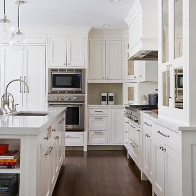 Kitchen - mid-sized transitional l-shaped dark wood floor kitchen idea in New York with a farmhouse sink, white cabinets, quartz countertops, gray backsplash, ceramic backsplash, paneled appliances, an island and recessed-panel cabinets