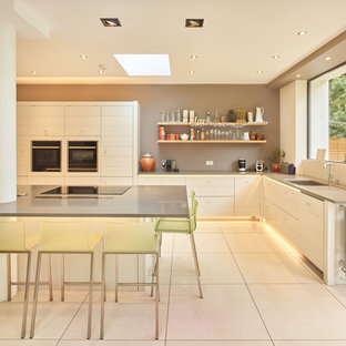 This is an example of a large modern l-shaped kitchen in West Midlands with a submerged sink, flat-panel cabinets, white cabinets, an island, white floors, grey worktops and stainless steel appliances.