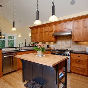 Example of an arts and crafts eat-in kitchen design in Seattle with stainless steel appliances, wood countertops, a single-bowl sink, shaker cabinets, medium tone wood cabinets, beige backsplash and travertine backsplash