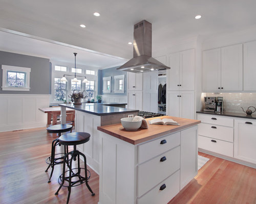 Craftsman eat-in kitchen idea in Seattle with wood countertops, shaker  cabinets, white