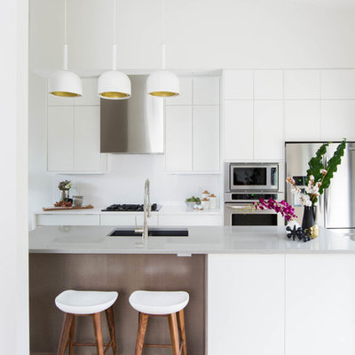 Mid-sized danish galley light wood floor open concept kitchen photo in Toronto with an undermount sink, flat-panel cabinets, white cabinets, quartzite countertops, white backsplash, stainless steel appliances and an island