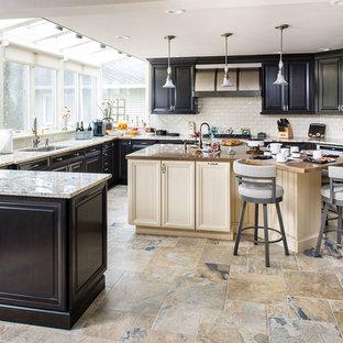 Idee per una grande cucina abitabile tradizionale con lavello sottopiano, ante con bugna sagomata, paraspruzzi beige, paraspruzzi con piastrelle in ceramica, elettrodomestici da incasso, isola e ante nere