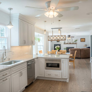 Large galley kitchen/diner in New York with a submerged sink, raised-panel cabinets, white cabinets, engineered stone countertops, white splashback, ceramic splashback, stainless steel appliances, plywood flooring and a breakfast bar.