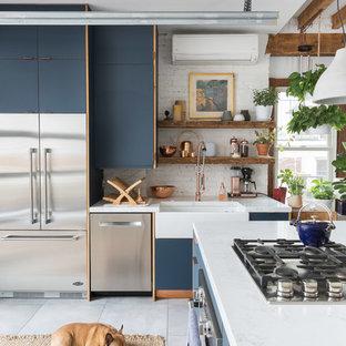 Modelo de cocina en L, bohemia, con fregadero sobremueble, armarios con paneles lisos, puertas de armario azules, salpicadero blanco, salpicadero de ladrillos, electrodomésticos de acero inoxidable, una isla, suelo gris y encimeras blancas