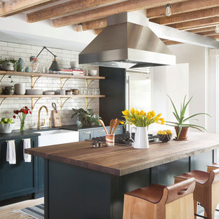 Inspiration for a large traditional galley open plan kitchen in New York with a belfast sink, open cabinets, white splashback, metro tiled splashback, stainless steel appliances, light hardwood flooring, an island, black cabinets, wood worktops and beige floors.