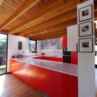 ロンドンの大きいモダンスタイルのおしゃれなキッチン (アンダーカウンターシンク、フラットパネル扉のキャビネット、赤いキャビネット、珪岩カウンター、白いキッチンパネル、レンガのキッチンパネル、黒い調理設備、淡色無垢フローリング、ベージュの床、白いキッチンカウンター) の写真