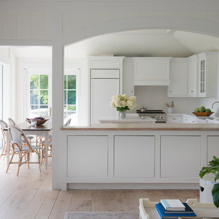 Inspiration for a large farmhouse galley kitchen/diner in San Francisco with a built-in sink, flat-panel cabinets, white cabinets, wood worktops, white splashback, stainless steel appliances, plywood flooring, an island, brown floors and brown worktops.