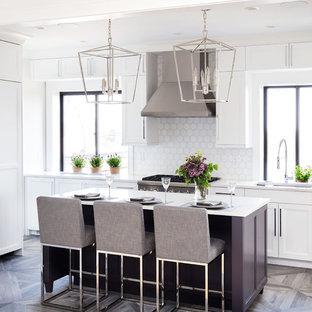 Foto di una piccola cucina lineare tradizionale chiusa con lavello sottopiano, ante bianche, paraspruzzi bianco, paraspruzzi con piastrelle a mosaico, elettrodomestici in acciaio inossidabile, pavimento in gres porcellanato, isola, pavimento marrone e top bianco