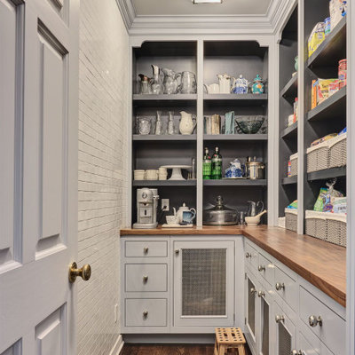 Kitchen pantry - traditional l-shaped dark wood floor and brown floor kitchen pantry idea in New York with recessed-panel cabinets, gray cabinets, wood countertops, no island and brown countertops