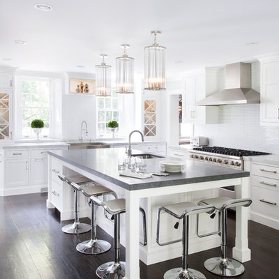 Large transitional l-shaped dark wood floor open concept kitchen photo in New York with a farmhouse sink, recessed-panel cabinets, white cabinets, white backsplash, quartz countertops, ceramic backsplash, stainless steel appliances and an island