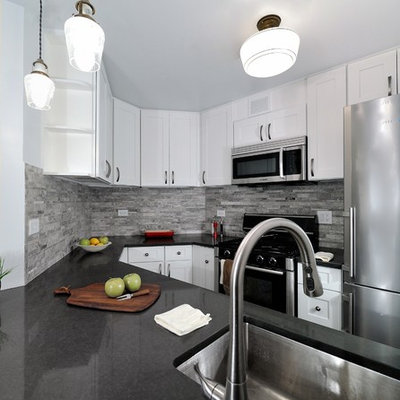 Enclosed kitchen - small transitional u-shaped enclosed kitchen idea in New York with a single-bowl sink, raised-panel cabinets, white cabinets, granite countertops, gray backsplash, stone tile backsplash and stainless steel appliances