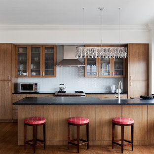 Mid-sized contemporary eat-in kitchen inspiration - Eat-in kitchen - mid-sized contemporary u-shaped medium tone wood floor eat-in kitchen idea in New York with a farmhouse sink, glass-front cabinets, medium tone wood cabinets and stainless steel appliances