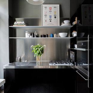 Foto på ett litet funkis kök, med en integrerad diskho, släta luckor, svarta skåp, bänkskiva i rostfritt stål, stänkskydd med metallisk yta och mörkt trägolv