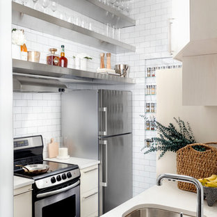 Inspiration for a small contemporary galley kitchen in New York with an undermount sink, open cabinets, stainless steel cabinets, white splashback, subway tile splashback and black floor.