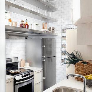 Immagine di una piccola cucina parallela design con lavello sottopiano, nessun'anta, ante in acciaio inossidabile, paraspruzzi bianco, paraspruzzi con piastrelle diamantate e pavimento nero