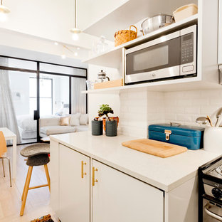 Example of a small trendy l-shaped light wood floor open concept kitchen design in New York with an undermount sink, open cabinets, white cabinets, quartz countertops, white backsplash, subway tile backsplash, paneled appliances and no island
