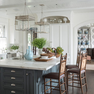 Example of a large classic u-shaped dark wood floor and brown floor kitchen design in Other with a farmhouse sink, recessed-panel cabinets, white cabinets, marble countertops, white backsplash, paneled appliances and an island