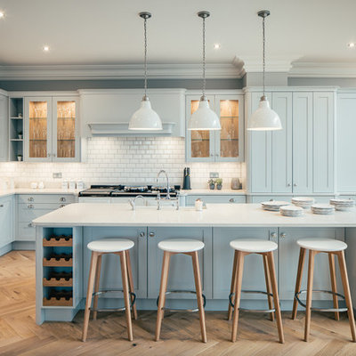Large transitional galley light wood floor and beige floor kitchen photo in Hertfordshire with blue cabinets, an island, shaker cabinets, white backsplash, subway tile backsplash and stainless steel appliances
