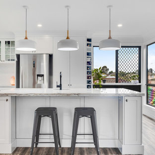 This is an example of a large transitional u-shaped eat-in kitchen in Sunshine Coast with an undermount sink, shaker cabinets, white cabinets, quartzite benchtops, white splashback, ceramic splashback, stainless steel appliances, vinyl floors, with island, white benchtop and brown floor.