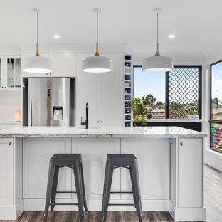 サンシャインコーストの大きいトランジショナルスタイルのおしゃれなキッチン (アンダーカウンターシンク、シェーカースタイル扉のキャビネット、白いキャビネット、珪岩カウンター、白いキッチンパネル、セラミックタイルのキッチンパネル、シルバーの調理設備の、クッションフロア、白いキッチンカウンター、茶色い床) の写真