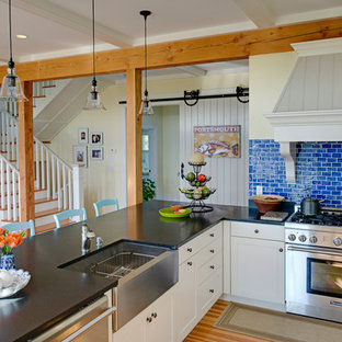 Example of a coastal l-shaped light wood floor open concept kitchen design in Boston with a farmhouse sink, shaker cabinets, white cabinets, blue backsplash, subway tile backsplash, stainless steel appliances and a peninsula