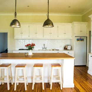 シドニーの大きいカントリー風おしゃれなキッチン (シェーカースタイル扉のキャビネット、白いキャビネット、木材カウンター、白いキッチンパネル、メタルタイルのキッチンパネル、シルバーの調理設備の、無垢フローリング) の写真