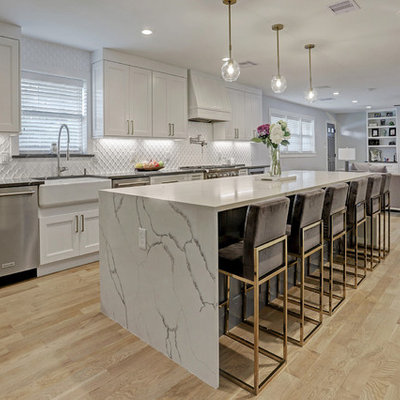 Example of a mid-sized transitional galley light wood floor and yellow floor eat-in kitchen design in Houston with a farmhouse sink, recessed-panel cabinets, white cabinets, quartz countertops, white backsplash, ceramic backsplash, stainless steel appliances, an island and white countertops