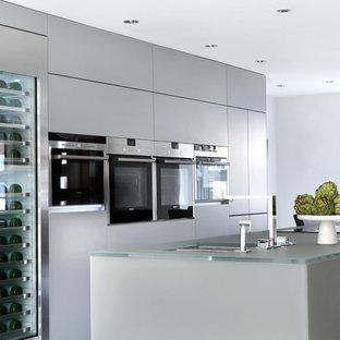 Ispirazione per una cucina design con lavello a doppia vasca, ante lisce, ante grigie, top in vetro, elettrodomestici in acciaio inossidabile e isola