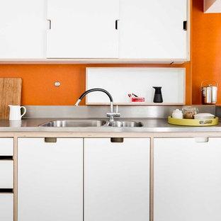 Ejemplo de cocina en U, contemporánea, de tamaño medio, cerrada, con armarios con paneles lisos, puertas de armario blancas, encimera de acero inoxidable, electrodomésticos de acero inoxidable, suelo de madera clara, una isla, suelo blanco, fregadero encastrado y salpicadero naranja