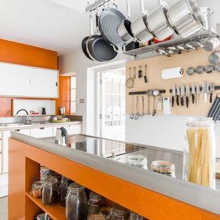 Inspiration for a mid-sized contemporary u-shaped separate kitchen in Other with flat-panel cabinets, white cabinets, stainless steel appliances, light hardwood floors, with island, a drop-in sink, orange splashback, stainless steel benchtops and white floor.