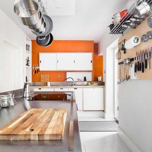 他の地域の中サイズのコンテンポラリースタイルのおしゃれなキッチン (フラットパネル扉のキャビネット、白いキャビネット、ステンレスカウンター、シルバーの調理設備の、淡色無垢フローリング、白い床、ドロップインシンク、オレンジのキッチンパネル) の写真