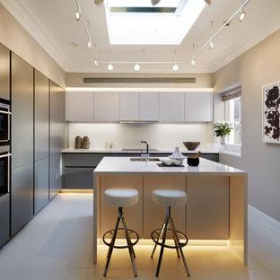 Пример оригинального дизайна: угловая кухня в современном стиле с врезной раковиной, плоскими фасадами, серыми фасадами, белым фартуком, техникой из нержавеющей стали и островом