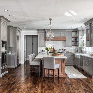 Inspiration for a transitional u-shaped medium tone wood floor and brown floor kitchen remodel in New York with a farmhouse sink, shaker cabinets, gray cabinets, white backsplash, subway tile backsplash, stainless steel appliances, an island and white countertops
