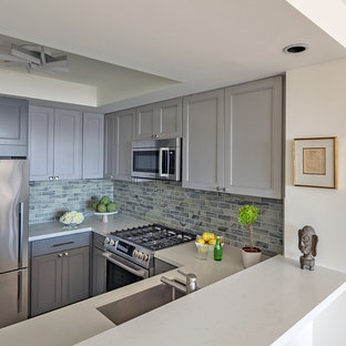This is an example of a small contemporary u-shaped eat-in kitchen in San Francisco with an undermount sink, shaker cabinets, grey cabinets, quartz benchtops, multi-coloured splashback, glass tile splashback, stainless steel appliances, linoleum floors, no island, brown floor and white benchtop.