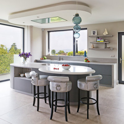 Example of a trendy galley kitchen design in Belfast with gray cabinets and an island