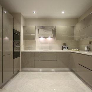 他の地域の中サイズのモダンスタイルのおしゃれなキッチン (ダブルシンク、フラットパネル扉のキャビネット、グレーのキャビネット、白いキッチンパネル、石スラブのキッチンパネル、黒い調理設備、セラミックタイルの床、アイランドなし) の写真