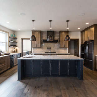 Transitional kitchen ideas - Example of a transitional u-shaped dark wood floor and brown floor kitchen design in Other with a farmhouse sink, recessed-panel cabinets, medium tone wood cabinets, beige backsplash, black appliances, an island and beige countertops