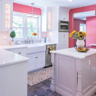Mid-sized transitional u-shaped eat-in kitchen in Philadelphia with a farmhouse sink, recessed-panel cabinets, white cabinets, quartz benchtops, white splashback, glass tile splashback, stainless steel appliances, porcelain floors, with island, grey floor and white benchtop.