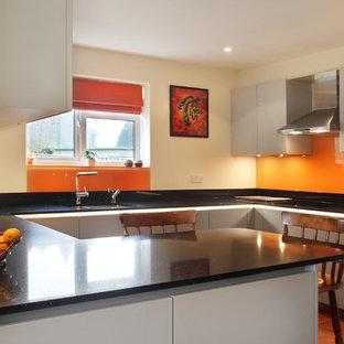 バッキンガムシャーの中くらいのコンテンポラリースタイルのおしゃれなキッチン (フラットパネル扉のキャビネット、グレーのキャビネット、珪岩カウンター、オレンジのキッチンパネル、ガラス板のキッチンパネル、シルバーの調理設備、テラコッタタイルの床、アンダーカウンターシンク) の写真
