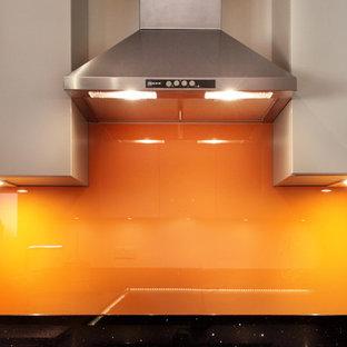 バッキンガムシャーの中サイズのコンテンポラリースタイルのおしゃれなキッチン (フラットパネル扉のキャビネット、グレーのキャビネット、珪岩カウンター、オレンジのキッチンパネル、ガラス板のキッチンパネル、シルバーの調理設備の、テラコッタタイルの床、アンダーカウンターシンク) の写真