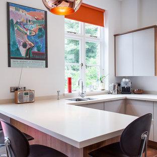 Kleine Stilmix Wohnküche in U-Form mit Unterbauwaschbecken, flächenbündigen Schrankfronten, grauen Schränken, Mineralwerkstoff-Arbeitsplatte, Küchenrückwand in Grau, Glasrückwand, Küchengeräten aus Edelstahl, Terrakottaboden und Halbinsel in Hertfordshire