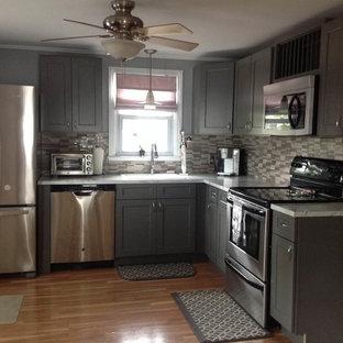 Imagen de cocina comedor en L, moderna, de tamaño medio, con fregadero encastrado, armarios estilo shaker, puertas de armario grises, encimera de mármol, salpicadero multicolor, salpicadero de azulejos de vidrio, electrodomésticos de acero inoxidable, suelo de madera clara y una isla