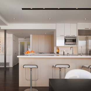 Inspiration for a small modern galley dark wood floor eat-in kitchen remodel in Los Angeles with stainless steel appliances, flat-panel cabinets, light wood cabinets, an undermount sink, solid surface countertops, white backsplash and an island