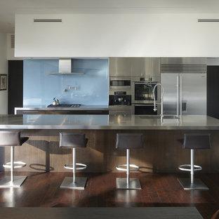 Modelo de cocina comedor de galera, minimalista, de tamaño medio, con fregadero integrado, encimera de acero inoxidable, salpicadero azul, salpicadero de vidrio templado, armarios con paneles lisos, electrodomésticos de acero inoxidable, una isla, suelo de madera oscura y puertas de armario en acero inoxidable