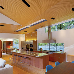 Mid-sized modern open concept kitchen photos - Mid-sized minimalist light wood floor open concept kitchen photo in San Francisco with stainless steel appliances, flat-panel cabinets, medium tone wood cabinets, stainless steel countertops and an integrated sink