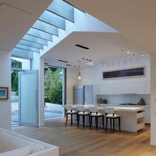 Inredning av ett modernt mellanstort kök, med släta luckor, vita skåp, glaspanel som stänkskydd, rostfria vitvaror, marmorbänkskiva, vitt stänkskydd, mellanmörkt trägolv och en köksö
