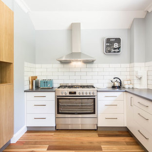 Inspiration for a mid-sized transitional u-shaped eat-in kitchen in Canberra - Queanbeyan with a drop-in sink, flat-panel cabinets, white cabinets, laminate benchtops, white splashback, porcelain splashback, stainless steel appliances, medium hardwood floors, beige floor and no island.