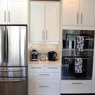Offene, Mittelgroße Moderne Küche in U-Form mit Doppelwaschbecken, Schrankfronten im Shaker-Stil, Quarzwerkstein-Arbeitsplatte, Küchenrückwand in Metallic, Küchengeräten aus Edelstahl, braunem Holzboden, Halbinsel und weißen Schränken in Vancouver
